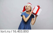 Купить «happy smiling girl in santa hat shaking gift box», видеоролик № 16403893, снято 12 декабря 2015 г. (c) Syda Productions / Фотобанк Лори