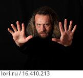 Купить «Мужчина с вытянутыми вперед руками на черном фоне», эксклюзивное фото № 16410213, снято 15 декабря 2015 г. (c) Яна Королёва / Фотобанк Лори
