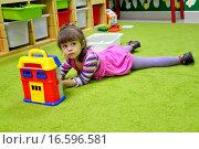 Купить «Маленькая девочка играет в детском саду, лежа на полу», фото № 16596581, снято 17 апреля 2014 г. (c) Ирина Борсученко / Фотобанк Лори