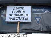 """Плакат с надписью """"Дайте людям спокойно работать!"""" на лобовом стекле грузового автомобиля на парковке дальнобойщиков в городе Химки, Россия (2015 год). Редакционное фото, фотограф Николай Винокуров / Фотобанк Лори"""