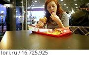Купить «Женщина ест гамбургер и картофель», видеоролик № 16725925, снято 6 декабря 2015 г. (c) Валентин Беспалов / Фотобанк Лори
