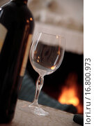 Купить «Bottle and glass of wine on a table in front of the fireplace, stillife», фото № 16800973, снято 17 июля 2019 г. (c) easy Fotostock / Фотобанк Лори