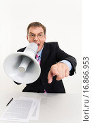Купить «Photo of businessman sitting at the table speaking through megaphone and pointing at camera», фото № 16866953, снято 22 июля 2019 г. (c) easy Fotostock / Фотобанк Лори