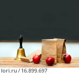 Купить «Lunch bags with apples and school bell on desk», фото № 16899697, снято 4 июня 2020 г. (c) easy Fotostock / Фотобанк Лори