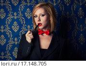 Купить «Молодая блондинка с красной помадой и галстуком-бабочкой в мужском пиджаке и с курительной трубкой», фото № 17148705, снято 15 ноября 2018 г. (c) Стивен Жингель / Фотобанк Лори