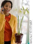 Купить «Black woman on cell phone admiring a flower», фото № 17177657, снято 18 февраля 2019 г. (c) easy Fotostock / Фотобанк Лори