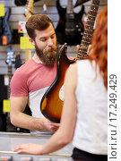 Купить «assistant showing customer guitar at music store», фото № 17249429, снято 11 декабря 2014 г. (c) Syda Productions / Фотобанк Лори