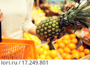 Купить «close up of woman with pineapple in grocery market», фото № 17249801, снято 20 декабря 2014 г. (c) Syda Productions / Фотобанк Лори