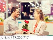 Купить «happy couple with present and flowers in mall», фото № 17250717, снято 10 ноября 2014 г. (c) Syda Productions / Фотобанк Лори