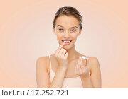 Купить «smiling young woman applying lip balm to her lips», фото № 17252721, снято 31 октября 2015 г. (c) Syda Productions / Фотобанк Лори