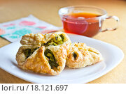 Ранний завтрак: крепкий чёрный чай в стеклянной чашке, булочки из слоёного теста с зелёным луком и яйцом, клубничка на белой тарелке. Размытый фон, фокус на пирожке. Стоковое фото, фотограф Александр Замоткин / Фотобанк Лори