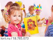 Купить «Девочка показывает аппликацию из цветной бумаги, которую она сделала на уроке творчества», фото № 18785073, снято 28 ноября 2015 г. (c) Сергей Новиков / Фотобанк Лори