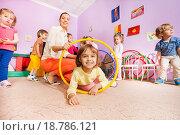 Купить «Маленькая девочка играет с другими детьми с обручами в классе детского сада», фото № 18786121, снято 28 ноября 2015 г. (c) Сергей Новиков / Фотобанк Лори