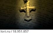 Купить «Нательный крестик на Библии», видеоролик № 18951857, снято 26 декабря 2015 г. (c) Сергей Мнацаканов / Фотобанк Лори