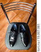 Купить «Мужские ботинки стоят на стуле», эксклюзивное фото № 19007981, снято 13 сентября 2015 г. (c) Игорь Низов / Фотобанк Лори