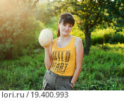 Купить «Миловидная женщина средних лет держит дыню в руке на прогулке», эксклюзивное фото № 19400993, снято 25 июля 2015 г. (c) Игорь Низов / Фотобанк Лори