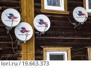 Спутниковые антенны Национальная спутниковая компания Триколор ТВ установлены на старинном деревянном доме в провинциальном городе России (2016 год). Редакционное фото, фотограф Николай Винокуров / Фотобанк Лори