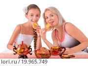 Купить «Mother and daughter eating pies», фото № 19965749, снято 22 апреля 2019 г. (c) easy Fotostock / Фотобанк Лори