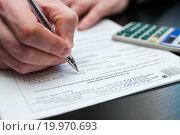 Купить «Бизнесмен рассчитывает налоговую декларацию за столом», эксклюзивное фото № 19970693, снято 10 января 2016 г. (c) Игорь Низов / Фотобанк Лори