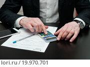 Купить «Бизнесмен рассчитывает на калькуляторе налоговую декларацию за столом», эксклюзивное фото № 19970701, снято 10 января 2016 г. (c) Игорь Низов / Фотобанк Лори