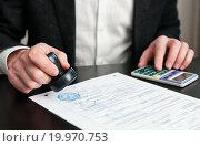 Купить «Бизнесмен ставит печать на документах», эксклюзивное фото № 19970753, снято 10 января 2016 г. (c) Игорь Низов / Фотобанк Лори