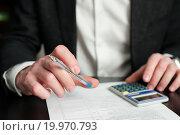 Купить «Бизнесмен с калькулятором и шариковой ручкой работает с документами», эксклюзивное фото № 19970793, снято 10 января 2016 г. (c) Игорь Низов / Фотобанк Лори