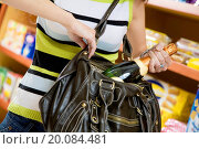Купить «woman in a supermarket stealing a bottle of champagne», фото № 20084481, снято 22 марта 2008 г. (c) easy Fotostock / Фотобанк Лори
