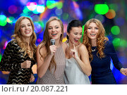 Купить «happy young women with microphone singing karaoke», фото № 20087221, снято 21 ноября 2015 г. (c) Syda Productions / Фотобанк Лори