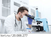 young scientist looking to microscope in lab. Стоковое фото, фотограф Syda Productions / Фотобанк Лори