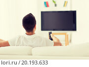 Купить «man watching tv and changing channels at home», фото № 20193633, снято 29 января 2015 г. (c) Syda Productions / Фотобанк Лори