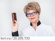 Купить «Пожилая женщина с улыбкой показывает таблетки», фото № 20205733, снято 13 декабря 2015 г. (c) Кекяляйнен Андрей / Фотобанк Лори