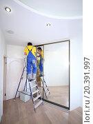 Купить «Young worker fixing mirrored door on sliding wardrobe in room», фото № 20391997, снято 23 апреля 2014 г. (c) Losevsky Pavel / Фотобанк Лори
