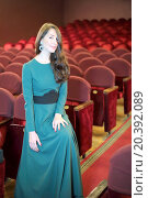 Купить «Beautiful young woman with dark long hair in a green evening dress in an empty auditorium with red seats», фото № 20392089, снято 12 марта 2014 г. (c) Losevsky Pavel / Фотобанк Лори