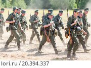Купить «NELIDOVO, RUSSIA- JULY 12, 2014: Battlefield 2014: group of Nazi soldiers go along the dusty road», фото № 20394337, снято 12 июля 2014 г. (c) Losevsky Pavel / Фотобанк Лори