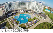 Купить «RUSSIA, SOCHI - JUL 25, 2014: Tourists get rest around and in pool of hotel Radisson Blu at summer sunny day. Aerial view. Photo with noise from action camera.», фото № 20396969, снято 25 июля 2014 г. (c) Losevsky Pavel / Фотобанк Лори