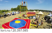 Купить «RUSSIA, NELIDOVO - JUL 12, 2014: Young boy jumps from tower to inflated deck during fair at sunny summer day. Aerial view. Photo with noise from action camera», фото № 20397085, снято 12 июля 2014 г. (c) Losevsky Pavel / Фотобанк Лори