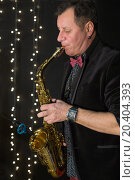 Купить «Saxophonist in a bow tie playing the saxophone in a club with garlands», фото № 20404393, снято 2 апреля 2014 г. (c) Losevsky Pavel / Фотобанк Лори