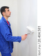 Купить «Worker in blue clothes paints by paint roller in new apartment», фото № 20404581, снято 11 декабря 2013 г. (c) Losevsky Pavel / Фотобанк Лори