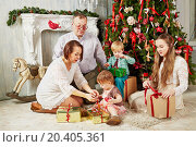 Купить «Family of five sits near Christmas tree untying ribbons on gift boxes», фото № 20405361, снято 26 декабря 2013 г. (c) Losevsky Pavel / Фотобанк Лори