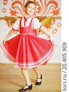 Купить «Beautiful girl in red folk costume dances near wall with pattern», фото № 20405909, снято 27 декабря 2013 г. (c) Losevsky Pavel / Фотобанк Лори