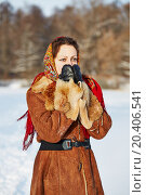 Купить «Young woman dressed in sheepskin fur coat and coloured shawl stands, hiding nose and chin in mittens against forest on bright frosty winter day», фото № 20406541, снято 17 января 2014 г. (c) Losevsky Pavel / Фотобанк Лори