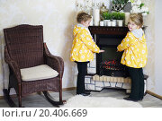 Купить «Two little girls in same clothes stands near fireplace and wicker rocking chair in cosy room. Focus on right girl.», фото № 20406669, снято 20 октября 2013 г. (c) Losevsky Pavel / Фотобанк Лори