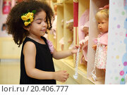 Купить «Little smiling girl touches dummy of toy doll in children store.», фото № 20406777, снято 18 мая 2013 г. (c) Losevsky Pavel / Фотобанк Лори
