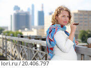 Купить «Pregnant woman in white dress holds cigar near railing in sunny day in city.», фото № 20406797, снято 19 июля 2013 г. (c) Losevsky Pavel / Фотобанк Лори