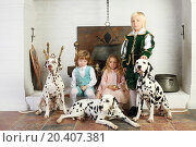 Купить «Two boys and girl in medieval costumes sit near fireplace with hanging pot with dalmatians.», фото № 20407381, снято 2 ноября 2013 г. (c) Losevsky Pavel / Фотобанк Лори