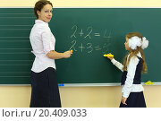 Купить «Girl and teacher stand near chalkboard and solve simple math examples in classroom at school.», фото № 20409033, снято 17 августа 2013 г. (c) Losevsky Pavel / Фотобанк Лори