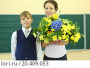 Купить «Happy teacher with big bunch of flowers and boy stand near chalkboard in classroom at school. Focus on boy.», фото № 20409053, снято 17 августа 2013 г. (c) Losevsky Pavel / Фотобанк Лори