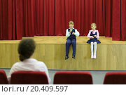 Купить «Happy son and daughter sit on stage with red curtains and mother looks at them. Focus on children.», фото № 20409597, снято 17 августа 2013 г. (c) Losevsky Pavel / Фотобанк Лори