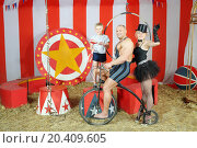 Three funny circus strong man, woman in cylinder and boy on retro bike with balloons in striped tent. Стоковое фото, фотограф Losevsky Pavel / Фотобанк Лори