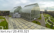 Купить «MOSCOW - OCT 23: View from unmanned quadrocopter to futuristic glass building of Main Greenhouse Botanical Garden with green lawns on October 23, 2013 in Moscow, Russia.», фото № 20410321, снято 23 октября 2013 г. (c) Losevsky Pavel / Фотобанк Лори